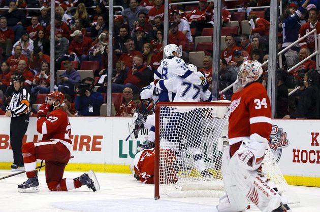 Hokejisté Tampy Bay slaví výhru ve čtvrtém zápase play off NHL nad Detroitem. Nahoře Ondřej Palát, v brance zklamaný Petr Mrázek.