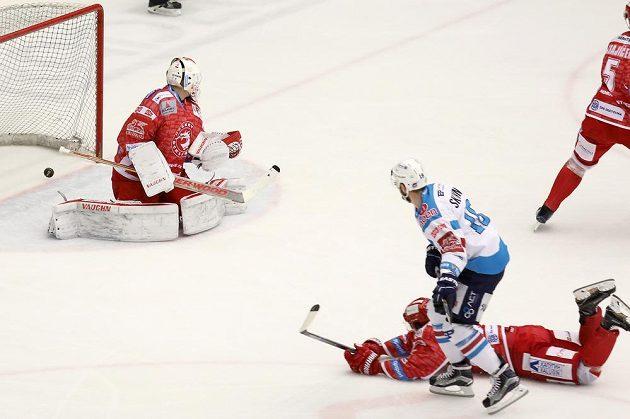 Chomutovský hráč David Skokan střílí gól, na ledě je Tomáš Netík, vlevo třinecký brankář Peter Hamerlík.