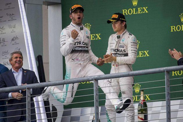 Lewis Hamilton juchá na pódiu v Austinu, Nico Rosberg s ledovým výrazem přihlíží.