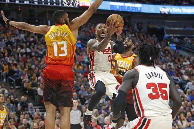 Lillard z Portlandu (uprostřed) se dere do koše mezi dvěma hráči soupeře.