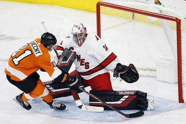 Hokejista Philadelphie Flyers Travis Konecny zakončuje útok těsně před Petrem Mrázkem z Caroliny.