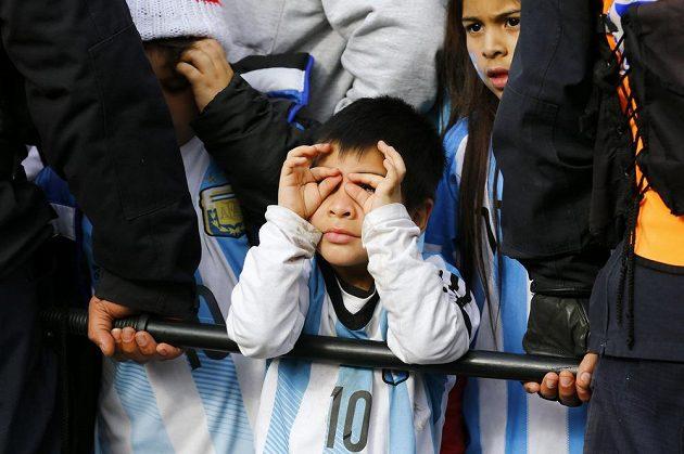 Malý fanoušek mezi policisty vyhlíží Lionela Messiho.