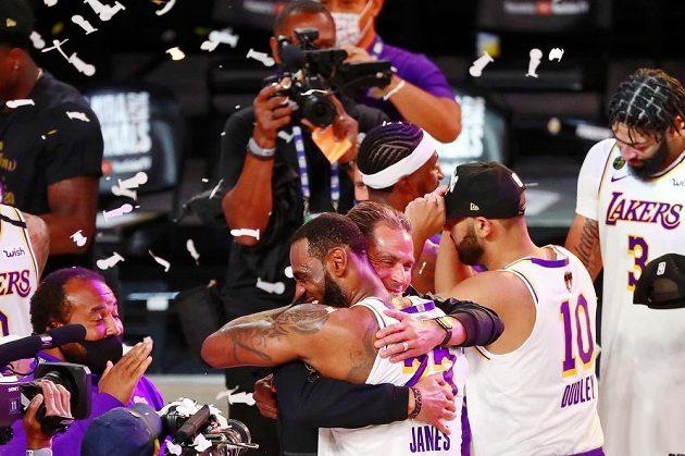 Hotovo. Vítězem NBA jsou basketbalisté Los Angeles Lakers. Hvězdný LeBron James (23) se objímá s generálním manažerem Robem Pelinkou.
