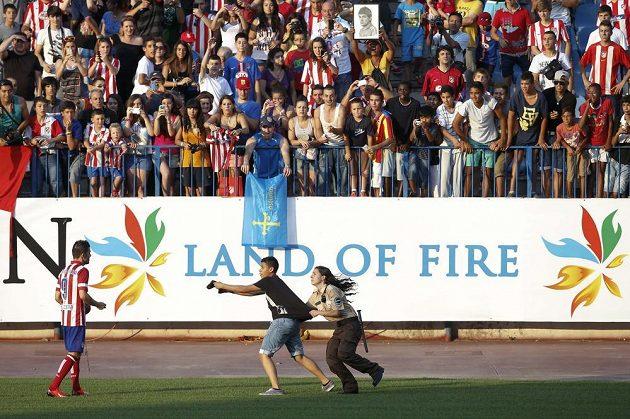 Ochranka se snaží zadržet fanouška, který se řítí k Davidu Villovi, jenž se představil příznivcům Atlétika v rámci mediální prezentace na stadiónu Vicente Calderóna v Madridu.
