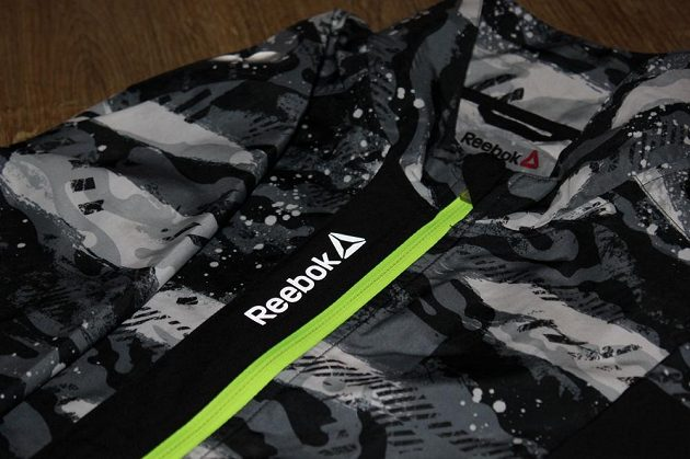 Větrovka Reebok Running Essentials Woven Jacket: Reflexní nápis zpředu.
