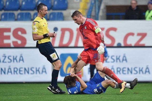 Liberecký útočník Matěj Pulkrab (v modrém dresu) leží na trávníku po zákroku olomouckého brankáře Miloše Buchty. Vlevo je rozhodčí Petr Ardeleánu.