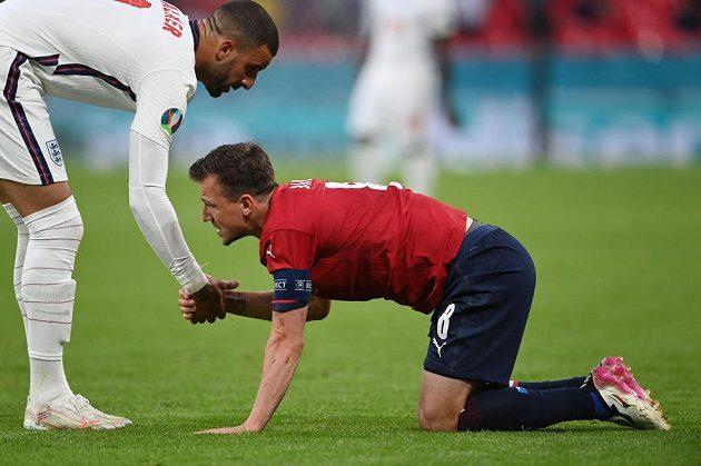 Angličan Kyle Walker pomáhá na nohy Vladimíru Daridovi.
