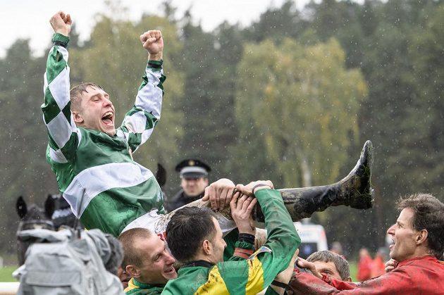 Vítězný žokej Jan Kratochvíl nad hlavami svých kolegů po triumfu ve Velké pardubické.