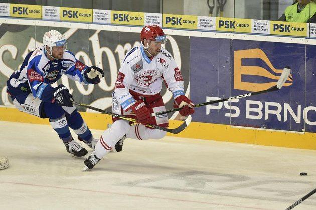 Martin Dočekal z Brna a Tomáš Linhart z Třince spěchají za pukem v utkání 27. kola hokejové extraligy.