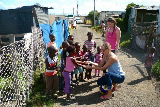 Kristýna Kolocová a Markéta Sluková (v podřepu) učí děti v jihoafrickém Guguletu volejbalovou techniku.