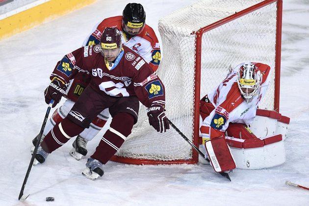 Sparťanský útočník Tomáš Rolinek (vpředu) se snaží protlačit před olomouckou branku. Vpravo přihlíží brankář Kohoutů Jiří Trvaj.