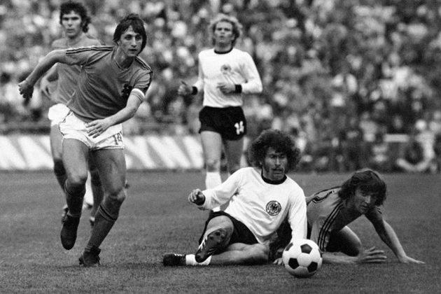 Nizozemec Johan Cruyff (vlevo) uniká podél sedícího německého fotbalisty Paula Breitnera ve finále MS na Olympijském stadiónu v Mnichově.