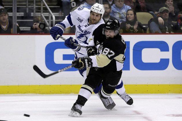 Sidney Crosby z Pittsburghu (v černém dresu) se dostal ke střele přes bránícího zadáka Tampy Bay Erica Brewera.