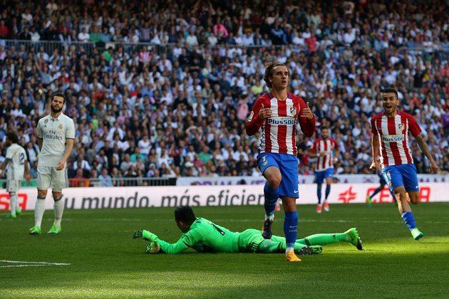 Antoine Griezmann se chystá odstartovat oslavy, právě dal gól do sítě Realu Madrid. Zápas o vládu nad městem skončil nerozhodně 1:1.