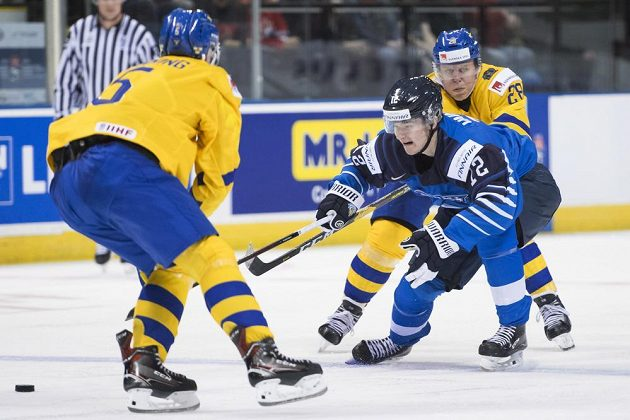 Finský hokejista Samuli Vainionpaa (12) se snaží prosadit přes švédského soupeře Adama Ginninga v utkání na MS hráčů do 20 let.