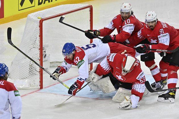 Michael Špaček padá ve skrumáži před švýcarskou brankou.