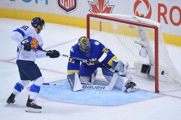 Fin Jussi Jokinen se snaží překonat švédského brankáře Henrika Lundqvista.