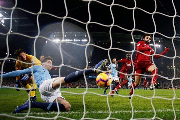 John Stones odvrací v pádu míč z brankové čáry před dotírajícím Mohamedem Salahem z Liverpoolu.