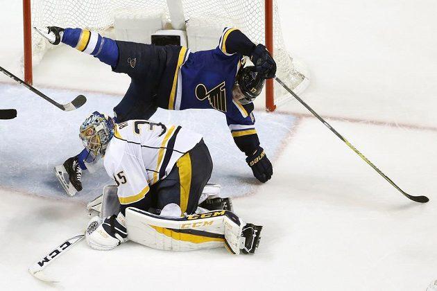 Forvard St. Louis Jaden Schwartz (17) padá po souboji s brankářem Nashvillu Pekka Rinnem (35).