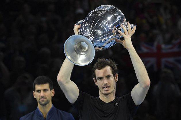 Andy Murray z Velké Británie s trofejí pro vítěze Turnaje mistrů. V pozadí poražený finalista Novak Djokovič ze Srbska.