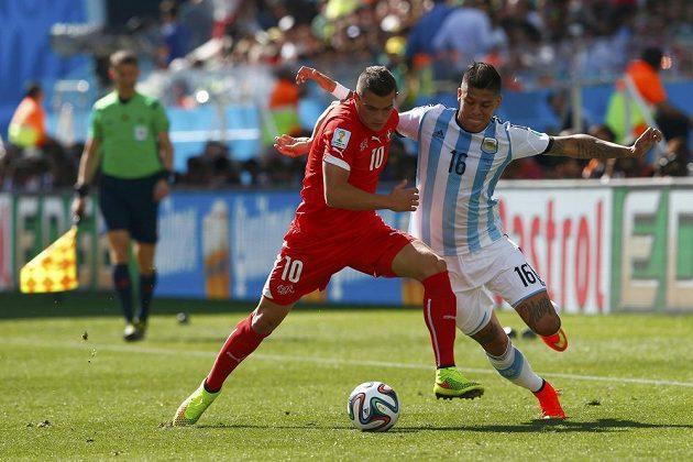 Švýcarský záložník Granit Xhaka (vlevo) nevyužil v prvním poločase velkou šanci. V tomto souboji bojuje o míč s argentinským obráncem Marcosem Rojem.
