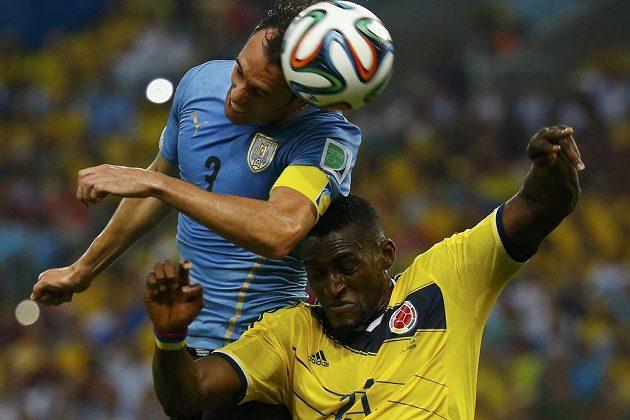 Uruguayský obránce Diego Godín (vlevo) v hlavičkovém souboji s Jacksonem Martínezem z Kolumbie.