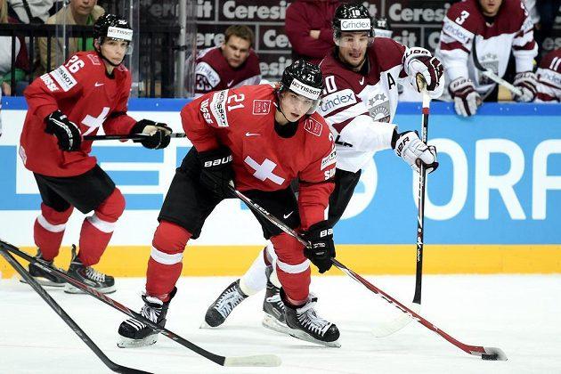 Švýcarský útočník Kevin Fiala (uprostřed) bráněný lotyšským útočníkem Laurisem Darzinsem během utkání hokejového mistrovství světa v Praze.