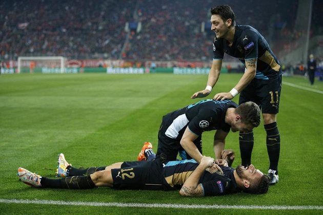Olivier Giroud (ležící na zádech) z Arsenalu jásá po druhém gólu proti Olympiakosu, nad ním Aaron Ramsey a Mesut Özil