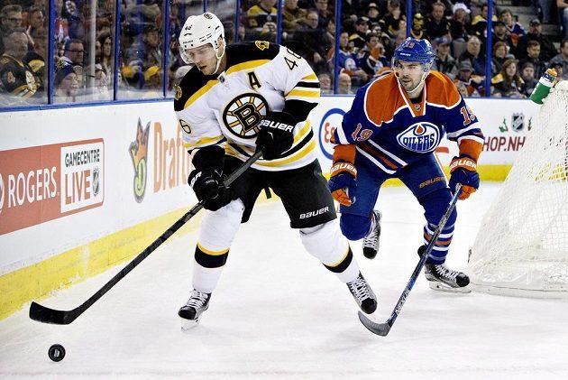 David Krejčí (vlevo) z Bostonu sledován Justinem Schultzem z Edmontonu.