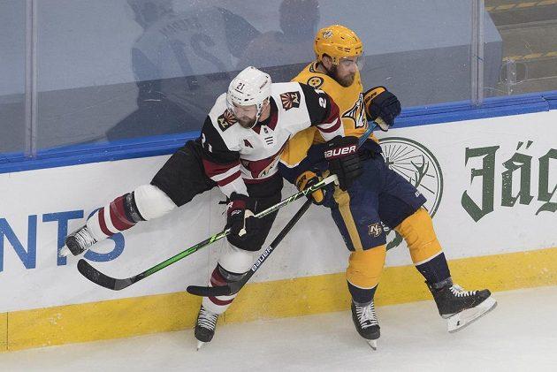 Yannick Weber (7) z Nashville Predators v souboji s hokejistou Arizony Coyotes Derekem Stepanem (21).
