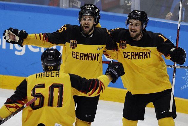 Německý střelec Felix Schütz slaví gól v síti Ruska ve finále olympijského turnaje se spoluhráči Patrickem Hagerem a Brooksem Macekem.