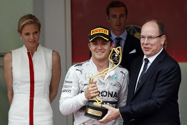 Nico Rosberg (uprostřed) dostává trofej pro vítěze GP Monaka od knížete Alberta II, jehož partenrka Charlene přihlíží v pozadí.