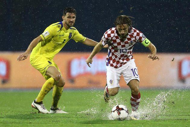 Chorvatský kapitán Luka Modrič si na podmáčeném trávníku vede míč před Enisem Alushim z Kosova.