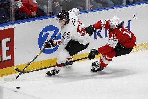 Rakouský hokejista Raphael Wolf a Švýcar Andres Ambühl v akci během utkání mistrovství světa.