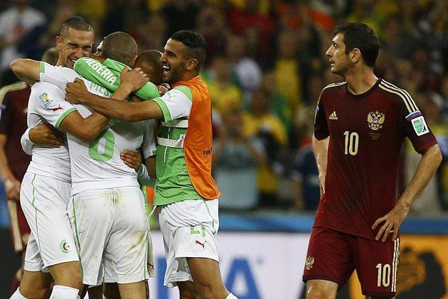 Fotbalisté Alžírska si vychutnávají postup do osmifinále MS, poprvé v historii dosáhli hráči afrického státu takového úspěchu. Vpravo je zklamaný Rus Alan Dzagojev.
