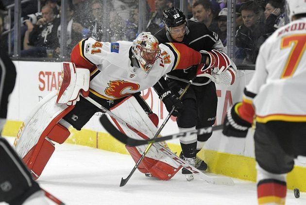 Brankář Calgary Flames Mike Smith se snaží za brankou zastavit centra Los Angeles Kings Trevora Lewise, který se hnal za pukem.