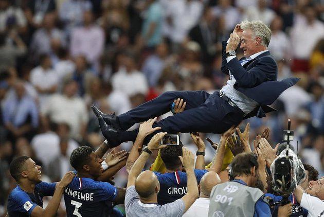 Francouzský trenér Didier Deschamps létá nad hlavami svých hráčů.