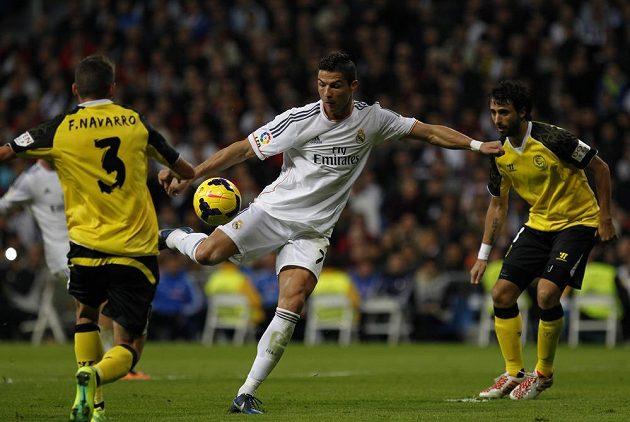 Cristiano Ronaldo (uprostřed) střílí na branku Sevilly.