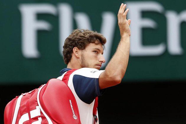 Španěl Pablo Carreňo Busta mává fanouškům poté, co musel vzdát duel s Rafaelem Nadalem.