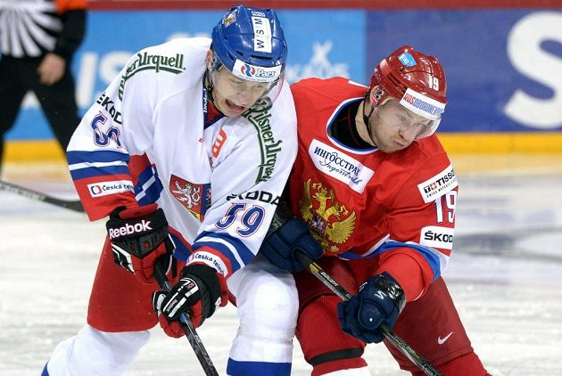 Český hokejista Lukáš Radil se bije o kotouč s Denisem Kokarevem z Ruska.