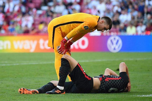 Chorvatský brankář Dominik Livakovič se sklání nad zraněným spoluhráčem Josko Gvardiolem.