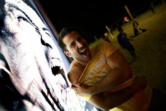 Jeden z fanoušků odhaluje rameno před reklamním billboardem, na němž uruguayský fotbalista Luis Suárez cení své bílé zuby.
