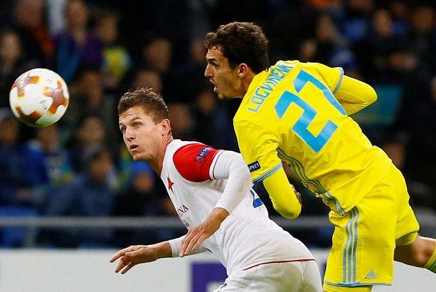 Útočník Slavie Tomáš Necid v souboji s Jurijem Logviněnkem z Astany v utkání Evropské ligy.