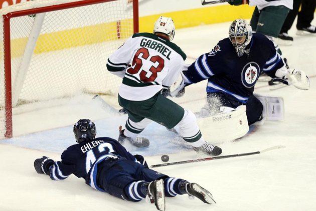 Brankář Winnipegu Ondřej Pavelec úspěšně zasáhl proti střele Kurtise Gabriela (63) z Minnesoty.