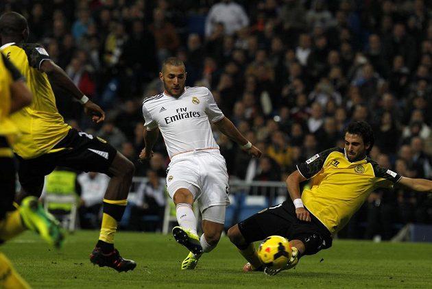 Karim Benzema (uprostřed) dává gól Realu, Stéphane M'Bia (vlevo) ani Nicolas Pareja (vpravo)ze Sevilly už zakročit nestačili.