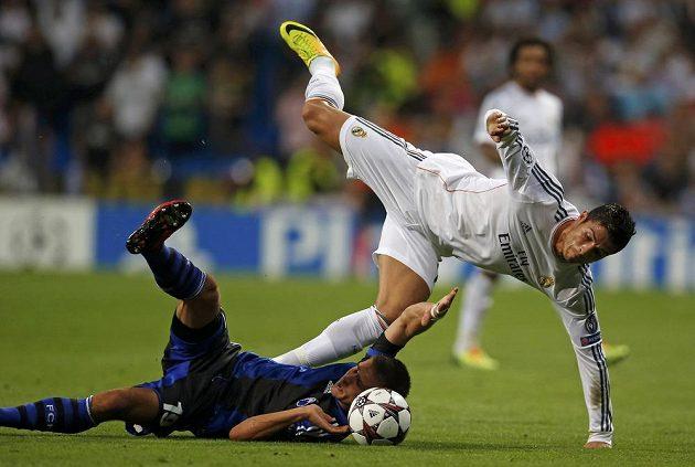 Rurik Gislason z Kodaně (dole) a Cristiano Ronaldo z Realu Madrid bojují o míč.