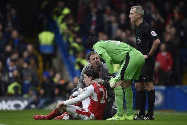 Petr Čech se sklání nad otřeseným Hectorem Bellerínem. Zadák Arsenalu nakonec musel po zákroku, jenž předcházel úvodnímu gólu Chelsea, střídat.