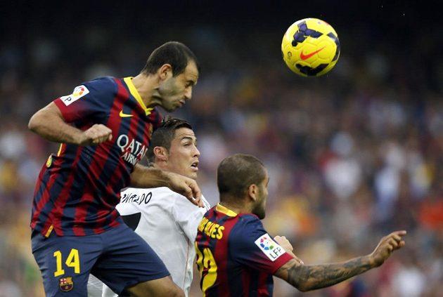 Javier Mascherano z Barcelony v hlavičkovém souboji s Cristianem Ronaldem.