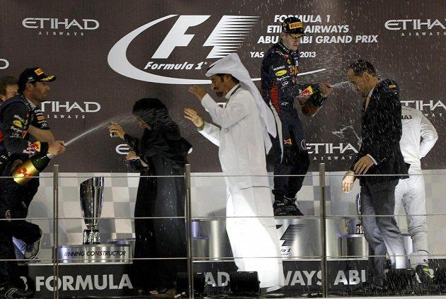 Nejlepší jezdci Velké ceny Abú Zabí kropí organizátory na stupních vítězů.