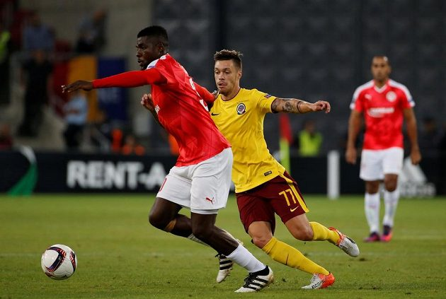 Fotbalista John Ogu z Beer Ševa se snaží odpoutat od Václava Kadlece ze Sparty.